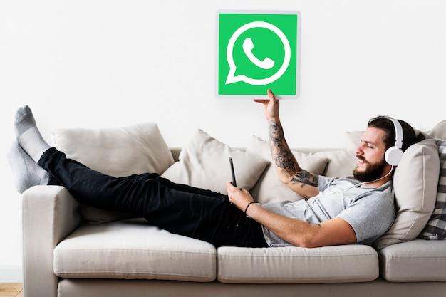 Uomo che mostra un'icona di whatsapp messenger