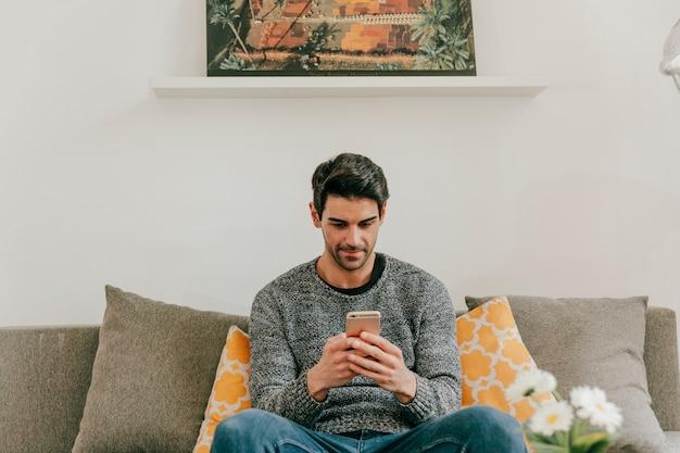 Uomo che naviga smartphone nel salotto