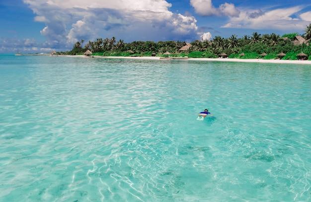 Uomo che nuota nell'oceano incredibilmente turchese