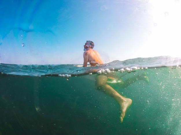 Uomo che nuota sulla tavola da surf in mare