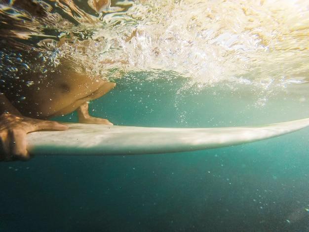 Uomo che nuota sulla tavola da surf nell'oceano