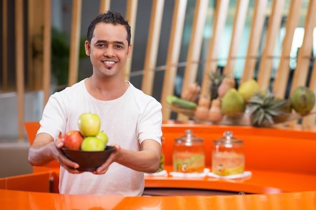 Uomo che offre una ciotola con le mele