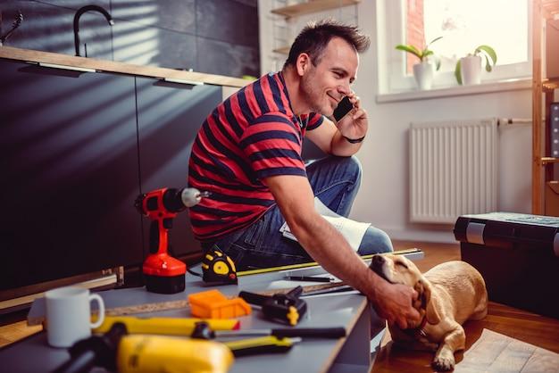 Uomo che ordina i materiali da costruzione al telefono