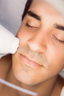 Uomo che ottiene un massaggio facciale alla clinica