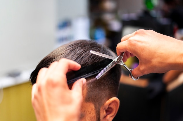 Uomo che ottiene un taglio di capelli con le forbici