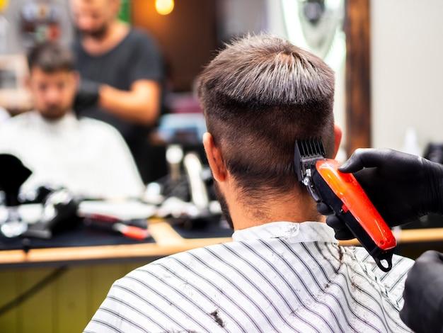Uomo che ottiene un taglio di capelli e una riflessione a specchio