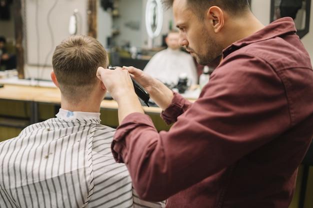 Uomo che ottiene un taglio di capelli in un barbiere
