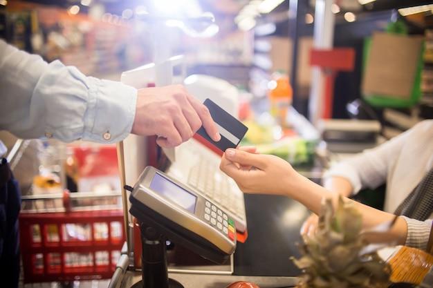 Uomo che paga con la carta di credito in supermercato