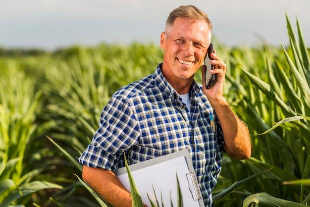 Uomo che parla al telefono in un campo