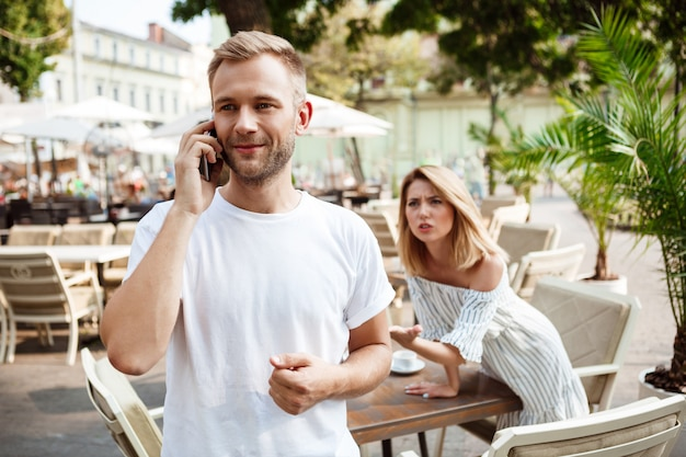 Uomo che parla al telefono mentre la sua ragazza è annoiata.
