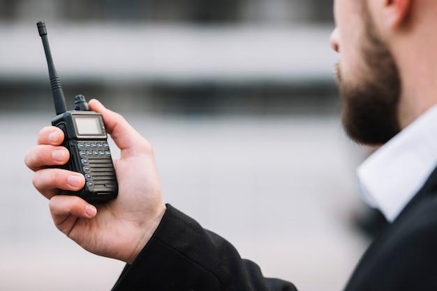Uomo che parla attraverso il walkie-talkie di sicurezza