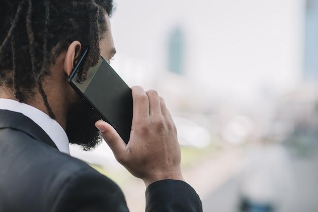Uomo che parla sulla vista posteriore del telefono