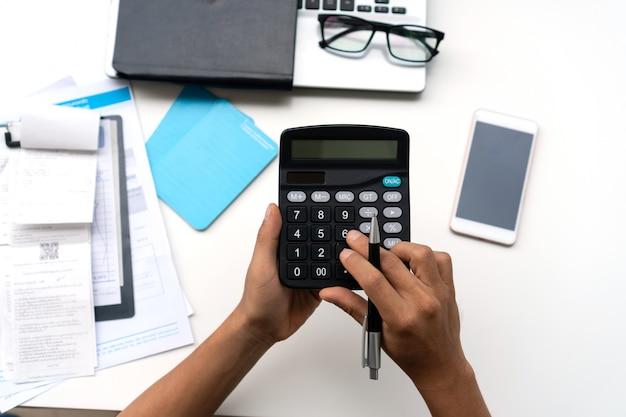 Uomo che per mezzo del calcolatore con fare l'ufficio di finanza a casa.