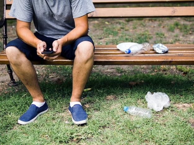 Uomo che per mezzo del cellulare che si siede sul banco vicino ai rifiuti di plastica al parco