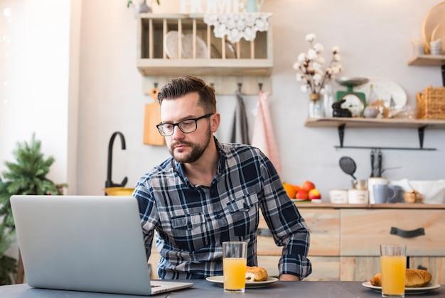 Uomo che per mezzo del computer portatile al tavolo della colazione