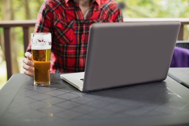 Uomo che per mezzo del computer portatile con bicchiere di birra sulla tavola