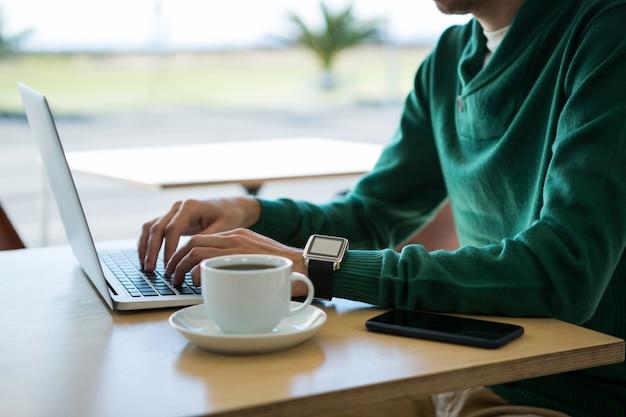 Uomo che per mezzo del computer portatile con la tazza di caffè e telefono cellulare sulla tavola