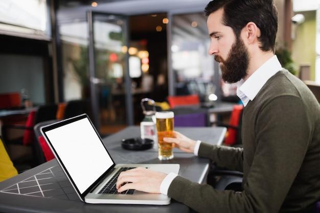 Uomo che per mezzo del computer portatile mentre mangiando bicchiere di birra