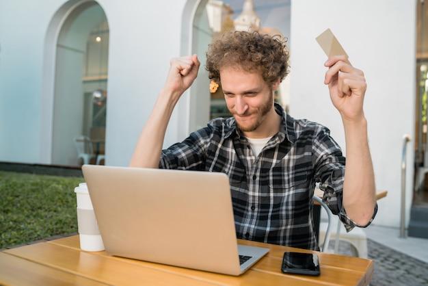 Uomo che per mezzo del computer portatile per acquistare online.