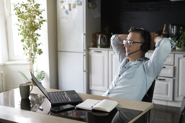 Uomo che per mezzo del computer portatile per lavorare online a casa