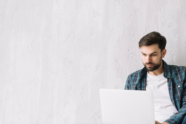 Uomo che per mezzo del computer portatile vicino alla parete