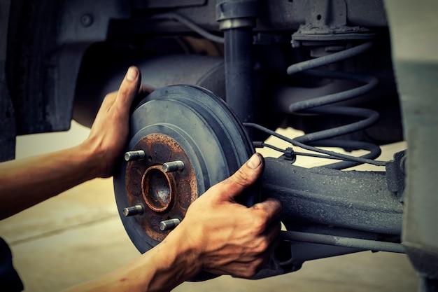 Uomo che per mezzo del meccanico di automobile blocca la ruota del vento. per controllare le gomme e il freno per l'auto. meccanico automatico preparazione per il lavoro.