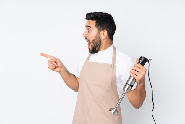 Uomo che per mezzo del miscelatore della mano isolato sulla parete bianca che indica dito il lato
