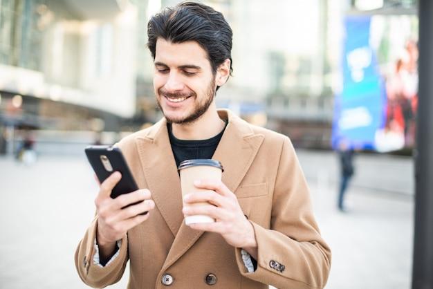 Uomo che per mezzo del suo cellulare e tenendo una tazza di caffè mentre camminando in una città