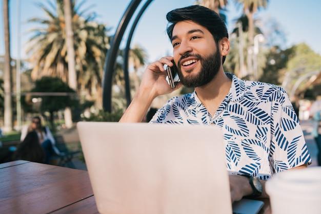 Uomo che per mezzo del suo computer portatile e parlando al telefono.