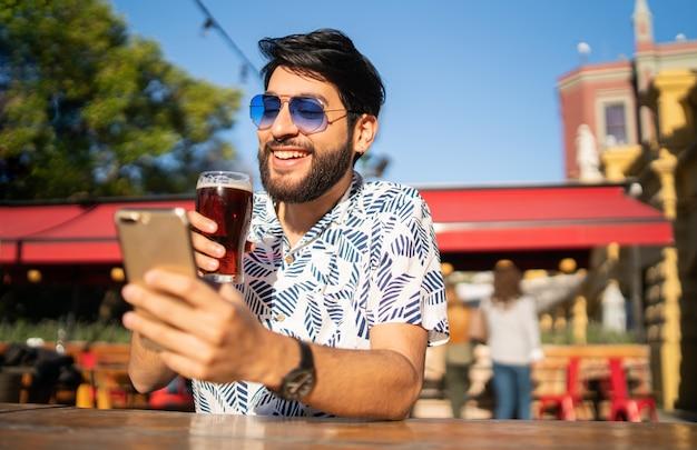 Uomo che per mezzo del suo telefono cellulare mentre bevendo birra.