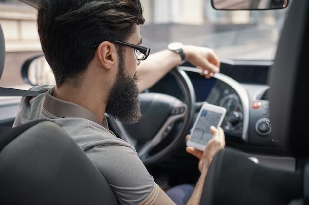Uomo che per mezzo del telefono cellulare mentre guidando.