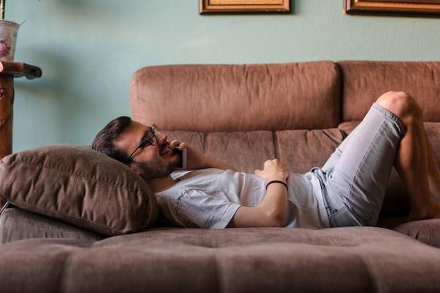 Uomo che per mezzo del telefono cellulare mentre trovandosi sul sofà a casa