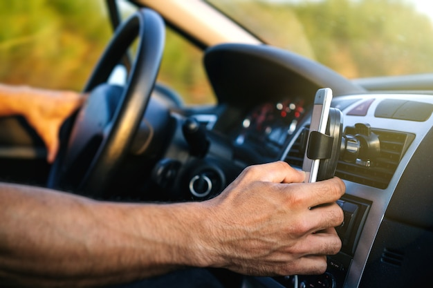 Uomo che per mezzo del telefono durante la guida