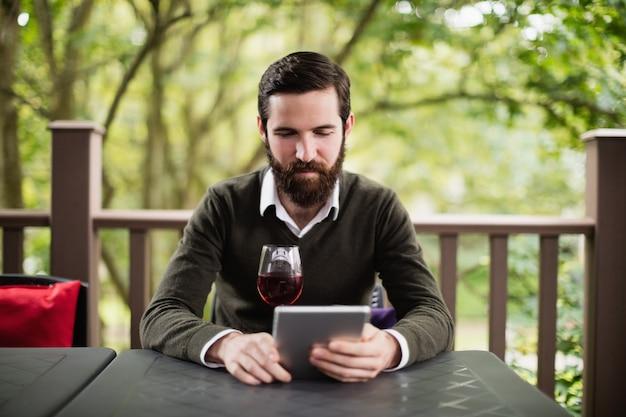 Uomo che per mezzo della compressa digitale mentre bevendo bicchiere di vino