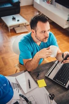 Uomo che per mezzo dello smart phone e tenendo la tazza di caffè