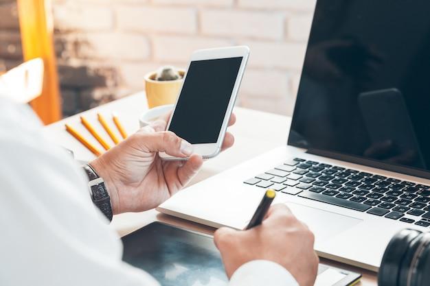 Uomo che per mezzo dello smart phone mobile. mani dell'uomo di affari facendo uso del telefono cellulare alla scrivania.
