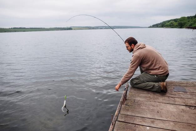 Uomo che pesca il pesce con la canna da pesca nel lago