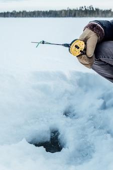 Uomo che pesca in inverno sul lago