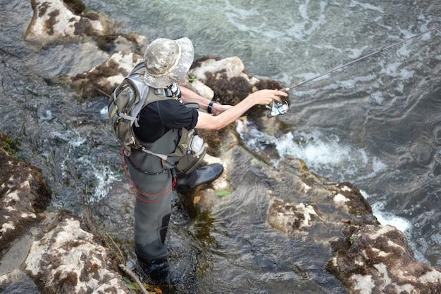 Uomo che pesca nel fiume. pescatore in acqua. pescatore mostra l'uso della tecnica di pesca. rod. hobby e attività sportive.