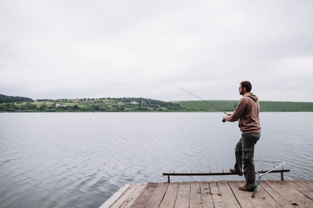 Uomo che pesca nel lago calmo
