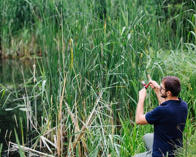 Uomo che pesca nel lago erboso