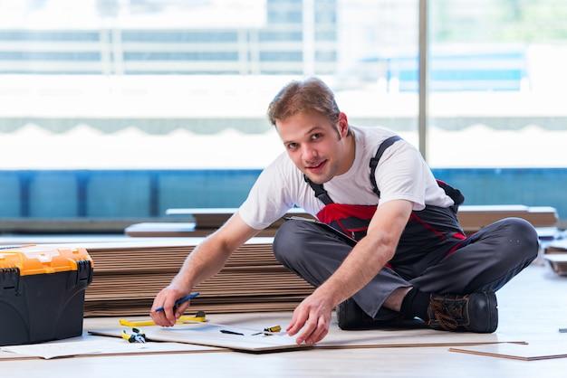Uomo che pone la pavimentazione laminata nel concetto della costruzione