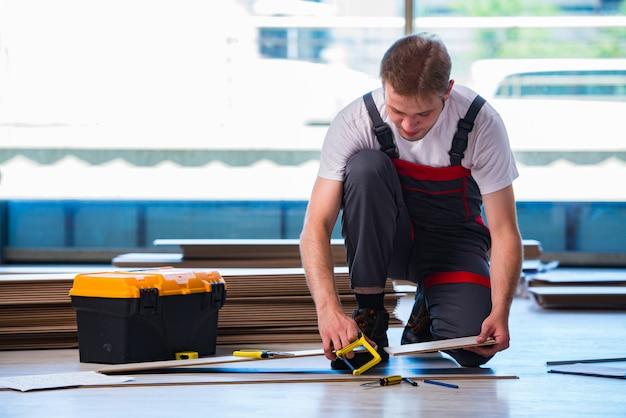 Uomo che pone la pavimentazione laminata nella costruzione