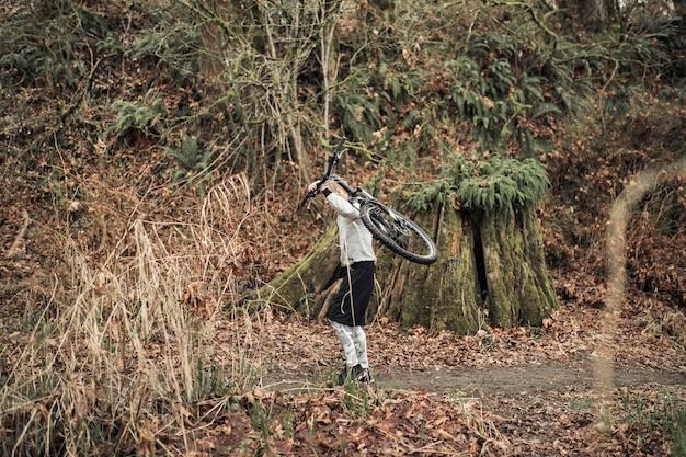 Uomo che porta la bicicletta sulla schiena nella foresta