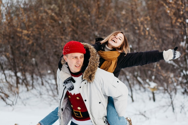 Uomo che porta la donna sulla schiena nella foresta di inverno