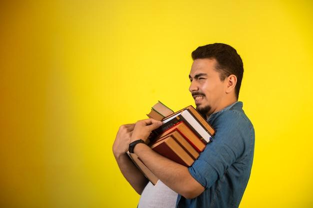 Uomo che porta una pila di libri pesanti.