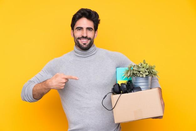 Uomo che porta una scatola piena di cose