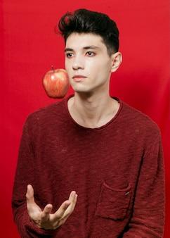 Uomo che posa con la mela a mezz'aria
