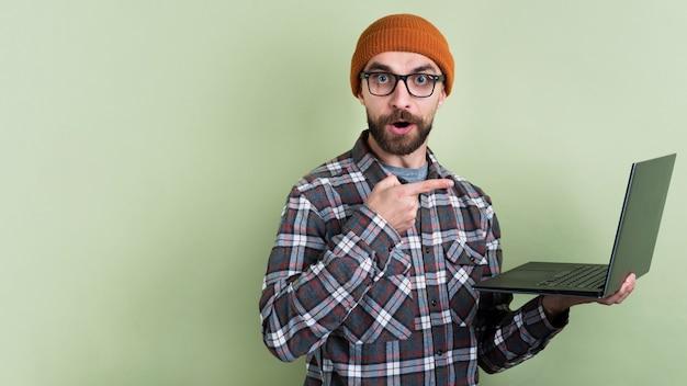 Uomo che posa e che indica al computer portatile