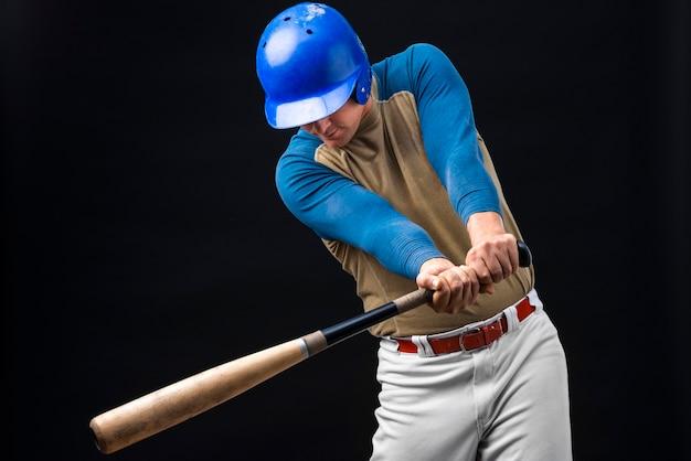 Uomo che posa nel casco con la mazza da baseball